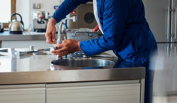 A shot of a man's hands working on a kitchen sink. He is wearing blue overalls with his tool kit in the background.